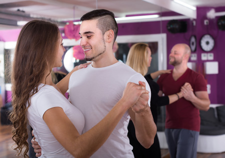Group of positive young adults dancing salsa in club