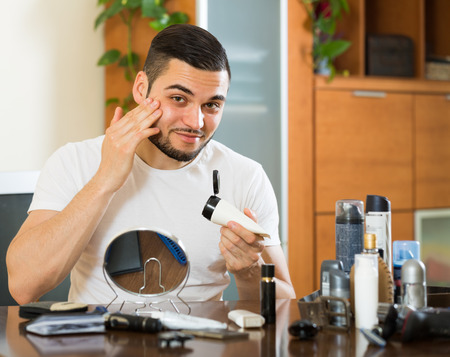 25s: Handsome man applying facial lotion at home Stock Photo
