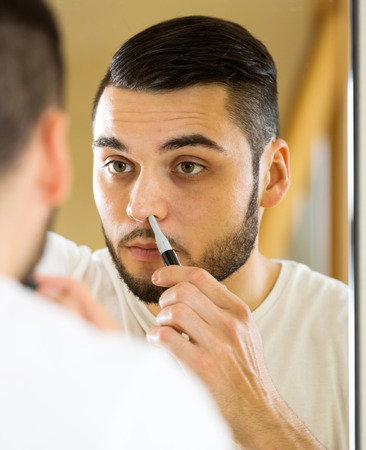 trims: portrait handsome adult man trims nose and ears hair at home Stock Photo