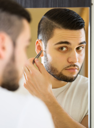 nostril: Guy looking at mirror and removing ear hair with tweezers