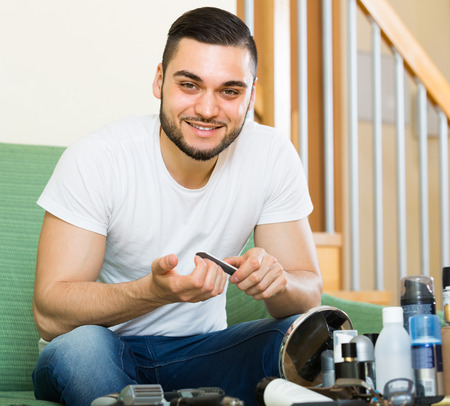 positiv: Young smiling handsome guy doing manicure at home