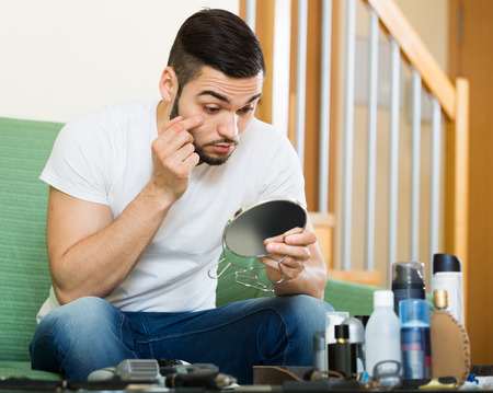 problematic: adult guy looking at his problematic skin in a mirror Stock Photo