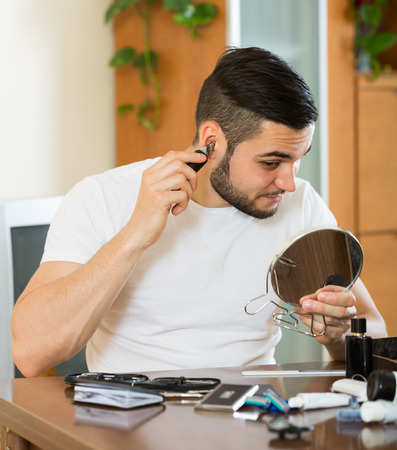30 years old: Guy 30 years old  remove hair from his nose and ears with trimmer