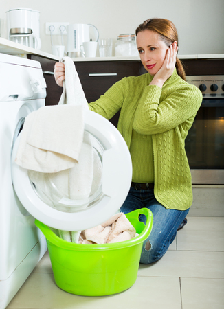 unsound: woman in green doing laundry with washing machine at home