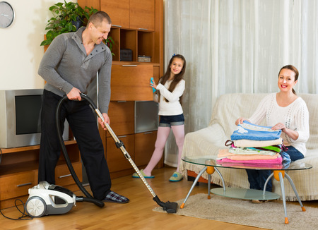 tidying up: Cheerful family of three tidying up a room all together. Focus on man Stock Photo