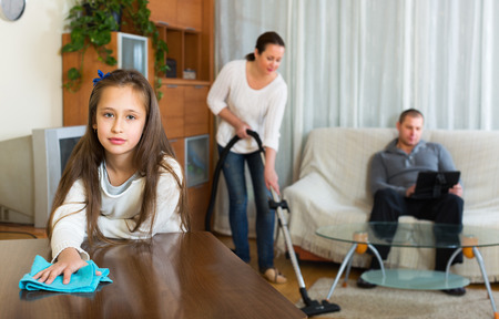 working man: Woman and girl doing general cleaning, man having rest