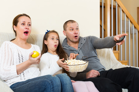 clothes interesting: Little girl and parent sitting with popcorn in front of TV. Focus on woman