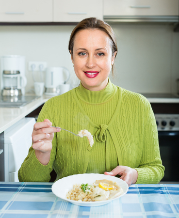 whitefish: Smiling housewife eating rice with filleted fish at kitchen