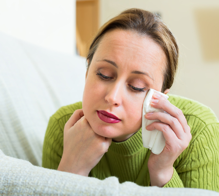 desperately: Desperately stressed woman on a sofa at home with a handkerchief in her hands and tears in her eyes