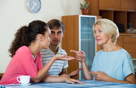 Young married couple and senior mother having bad discussion Stock Photo