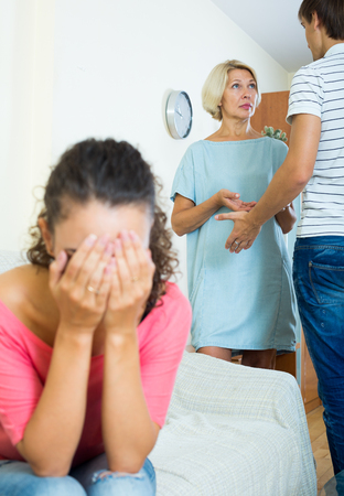 husband: Frustrated young woman taking hard argue between husband and mother