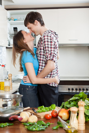 intimate sex: Young loving couple hugging in kitchen Stock Photo