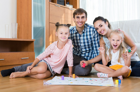 Little spanish girls playing with parents at board game on floor Stock Photo - 46021571