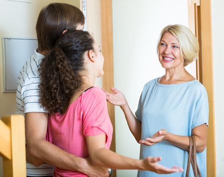 mujeres felices: Pareja joven de la familia madre senior de bienvenida en la puerta y sonriendo Foto de archivo