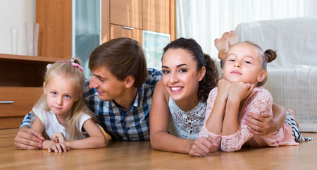 4s: Happy young parents with two little daughters laying on the floor at home