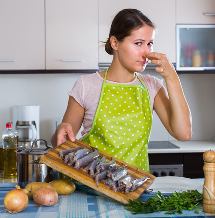 disgusting: Young housewife cooking fish and wincing of disgusting smell
