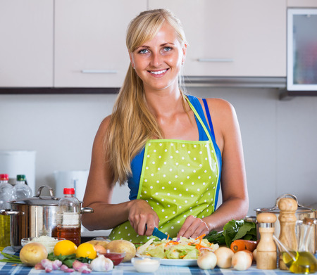 kitchen spanish: Cheerful long-haired spanish blondie preparing veggies in domestic kitchen