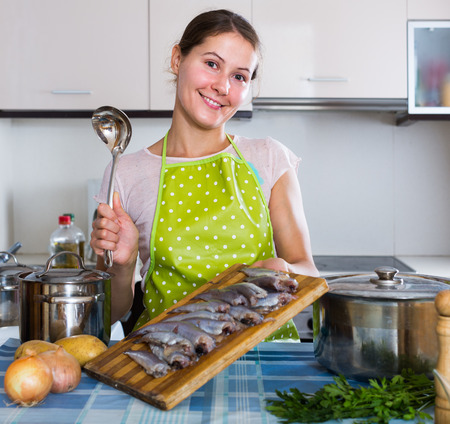 loathsome: Happy spanish housewife trying new recipe of sprattus in kitchen