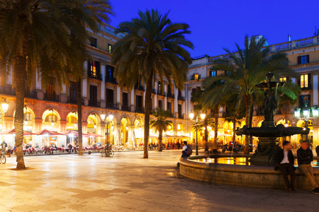View of Placa Reial with fountain and restaurants in evening. Barcelona, Catalonia Stock Photo