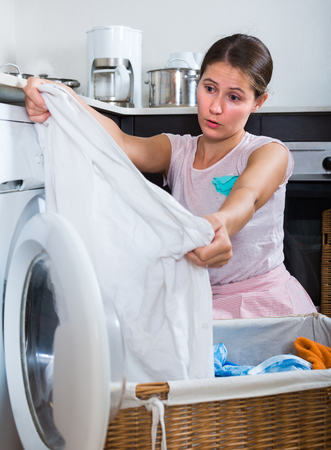 Upset young woman with musty linen after laundry at kitchen
