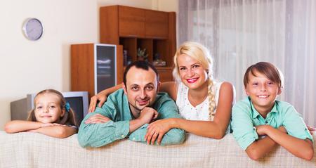middle class: Retrato de la sonrisa familia de clase media con dos hijos en el hogar. Centrarse en el hombre