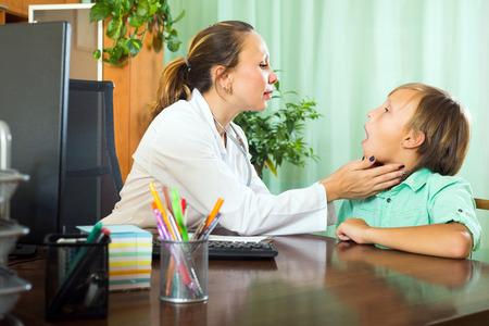 personne malade: Bienvenus femme m�decin d'examiner la gorge du jeune gar�on � la clinique Banque d'images
