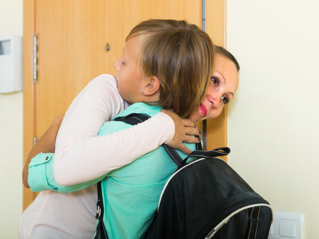 reprimand: Mother gives admonitions to teenager son and saying goodbye at doorway Stock Photo