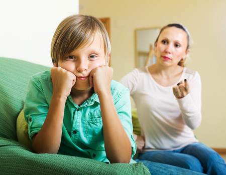 Ordinary mother scolding sad teenager son in living room at home Stock Photo