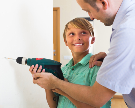 modifying: Smiling teenager assist father to using electric drill wall at home Stock Photo
