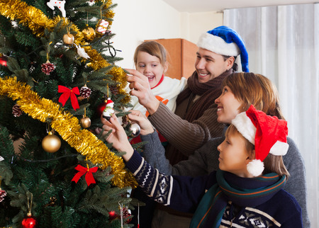 home decorating: parents with children decorating Christmas tree at home
