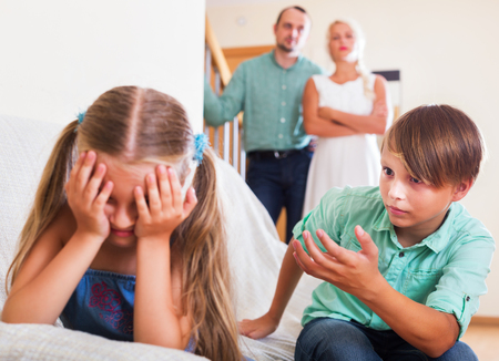 abusing: A little sister and brother abusing each other, a parents standing near them at home