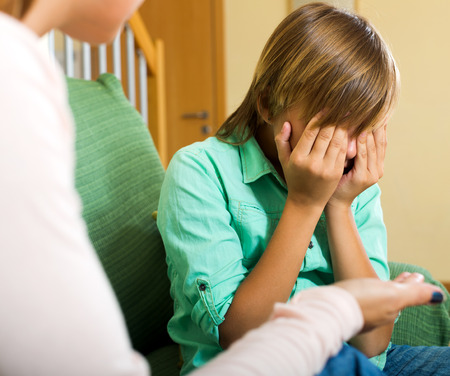 fracas: Angry mother scolding crying teenage son in living room at home