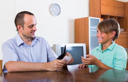money pocket: Muchacho sonriente adolescente pidiendo pap� para la peque�a de dinero de bolsillo en casa