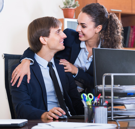 subordinate: Top manager flirting with happy adult  subordinate official at workplace