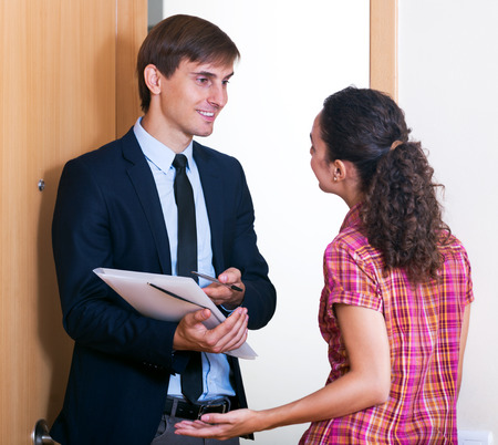 doors: Attractive agent with documents and potential client talking near door