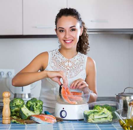 Positive young woman cooking trout in steamer for healthy lunch