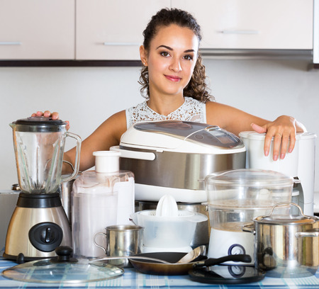 domestic: Positive housewife with culinary devices posing at domestic kitchen