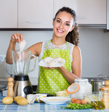 liquidiser: Portrait of smiling girl making delicious croquettes using blender at home