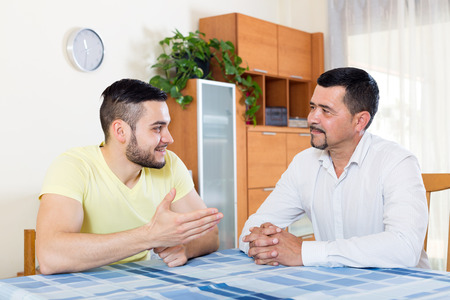 adult intercourse: two men sitting at a table talking in the living room