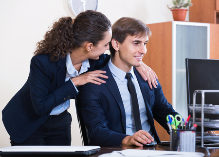 tempter: Top manager flirting with smiling american adult subordinate official at workplace
