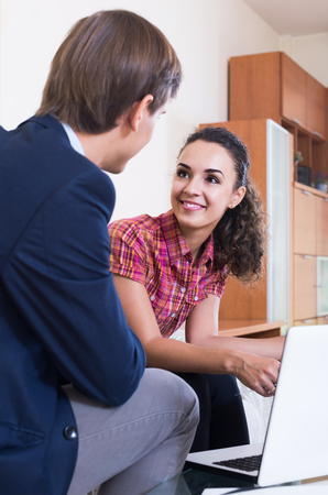 insurance agent: adult insurance agent and customer discussing agreement terms and smiling Stock Photo