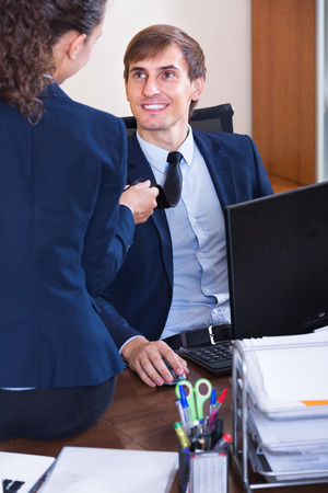 tempter: Playful flirting between smiling managers at work in office