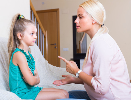 mischievous: Strict young mother scolding mischievous little daughter at home Stock Photo