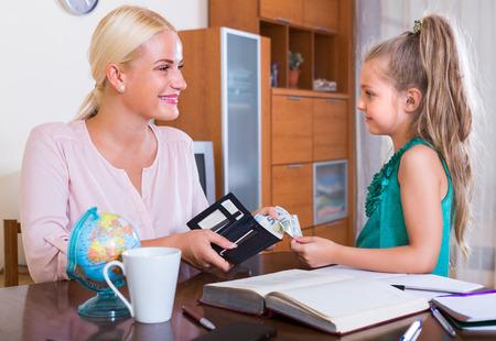 bolsa dinero: Asignaci�n de dinero de bolsillo: linda ni�a y la madre con el monedero Foto de archivo