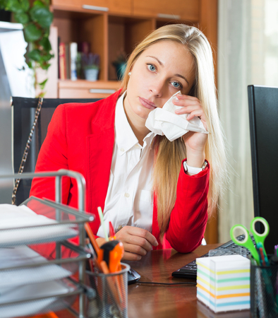 complications: sad blonde crying sitting at the table in the workplace