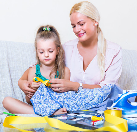 mother child: Portrait of positive mom and child with sewing kit at home