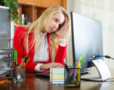 complications: tired young blonde woman with office work sitting at the computer Stock Photo