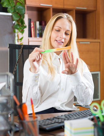unbearable: Bored businesswoman polishing nails at office desk