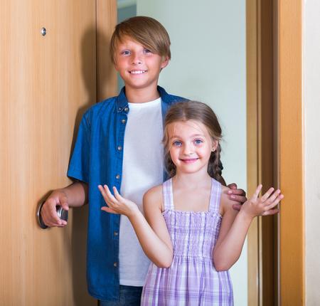 threshold: Smiling teenage boy and little girl standing near opened door