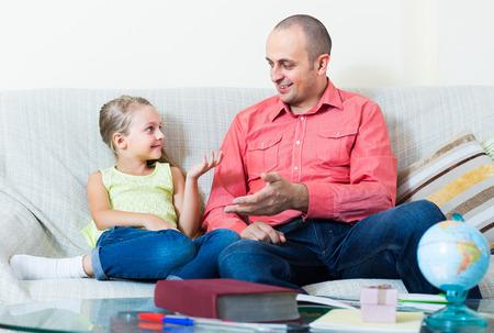 personas hablando: Retrato de padre estadounidense feliz y ni�a en el interior de discutir algo divertido.